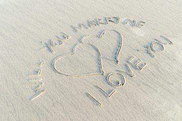 valentine's day proposal written on sand