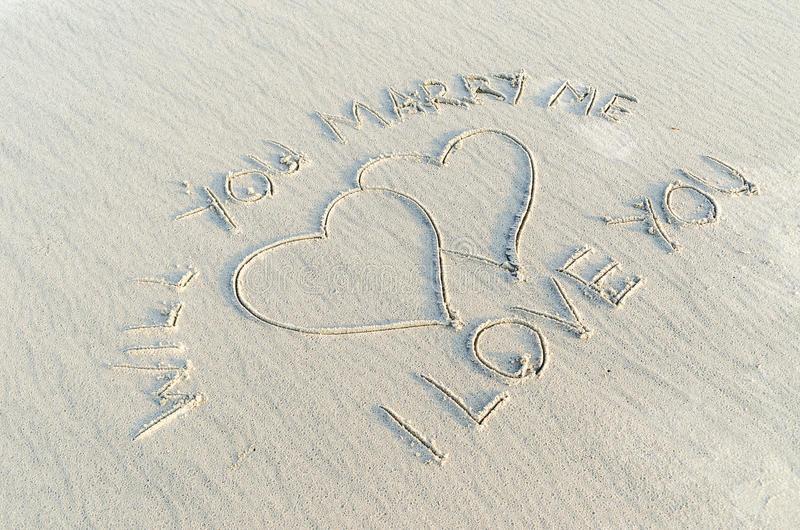 valentine's day proposal written on sand
